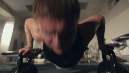 Sweaty man pushed from floor with dumbbells in the gym