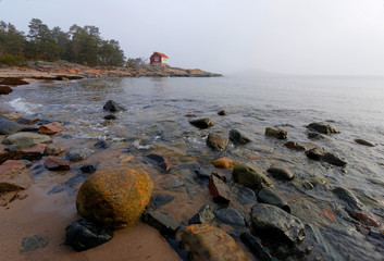 Coast line and small red cottage