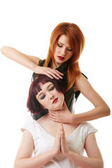 Sexy red-haired woman doing neck massage to girl