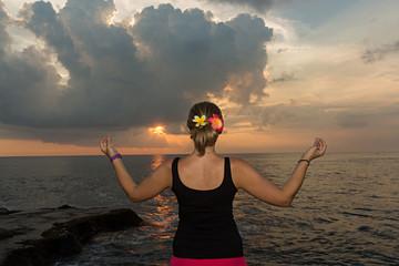 Mujer haciendo meditación al atardecer en el mar.