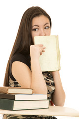 Asian American female student covering mouth with her book