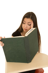 Female student reading a big book falling asleep