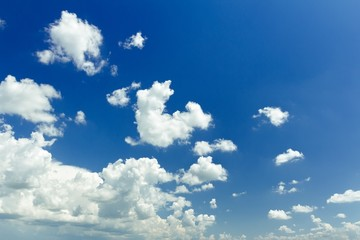 Blue ultramarine sky background with white ethereal cumulus