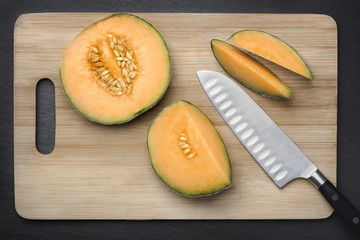 Cut sugar melon on a chopping board.