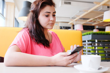 Portrait of beautiful women using her mobile phone in cafe.