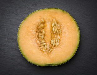 Sliced musk melon isolated on slate.