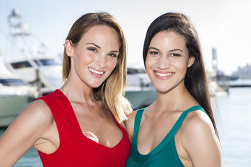 Two women posing in marina harbor, yachts on background.