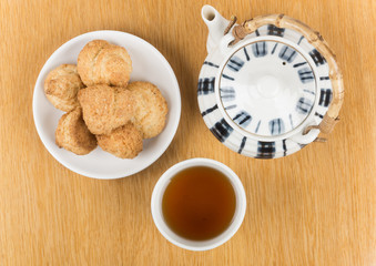 Porcelain teapot, cup of tea and biscuits on  saucer isolated on