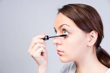 Attractive woman applying dark mascara