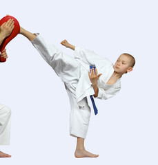 Boy trains kick in the head on a grey background
