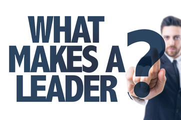 Business man pointing the text: What Makes a Leader?