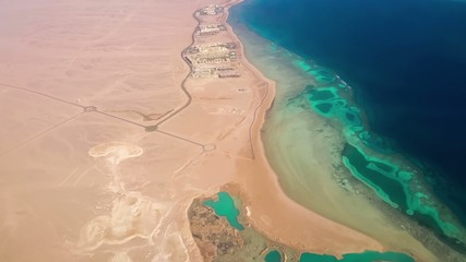 Aerial View from the Aircraft to Desert and Sea, sunny day