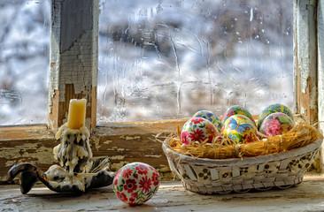 Корзина с пасхальными яйцами на подоконнике, и свеча.