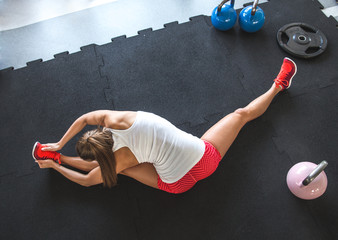 Woman worming up and stretching her body at the gym