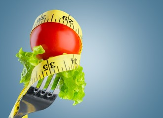 Diet. Small ripe tomato on fork with a measuring tape