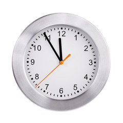 Round clock shows five minutes to twelve