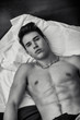 Attractive shirtless athletic young man laying in bed at night - 81315820