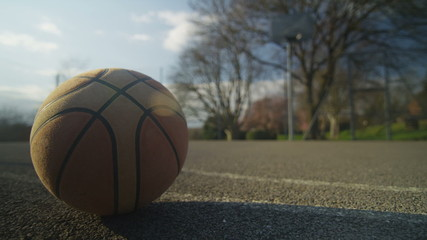 Basketball on an empty court outdoors