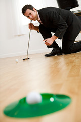 Business: Businessman Playing Golf In Office