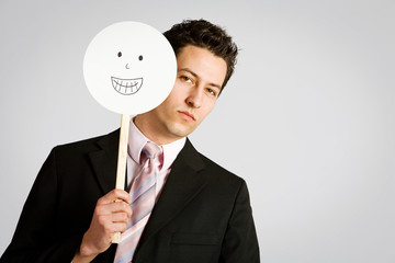 Disguise: Unhappy Businessman Behind Happy Mask