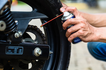 Man greasing motorcycle chain