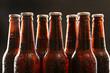 Leinwanddruck Bild - Glass bottles of beer on dark background