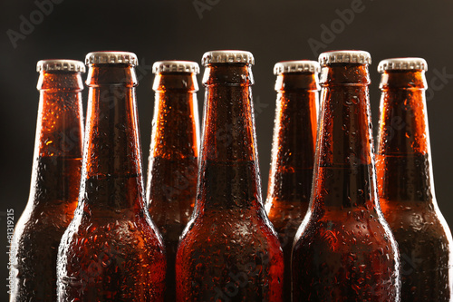 Poster Alcohol Glass bottles of beer on dark background