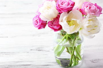 Bouquet of fresh roses and tulips on wooden background