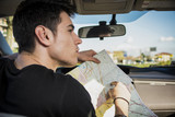 Gorgeous Young Man Inside Car Asking for Directions Holding a