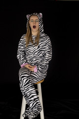 Young female model wearing cat pajamas yawning and sitting on st