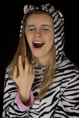 close up portrait of a young woman yawning in cat pajamas