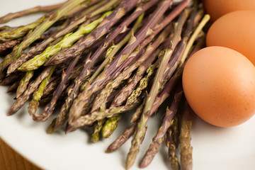 Fresh wild asparagus on a plate with eggs  ready to be cooked