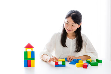 young asian woman playing building block