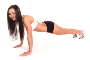 Beautiful young woman exercising in a fitness center - Pushup