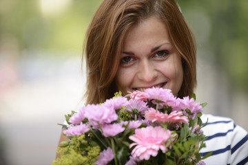 Happy woman holding floral arrangement
