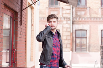 Handsome businessman in leather jacket speaking on the phone
