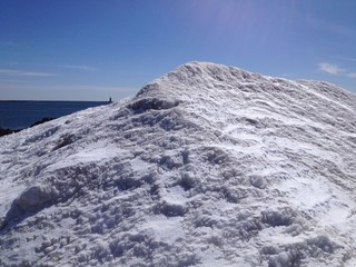 tiny lighthouse behind the snow bank
