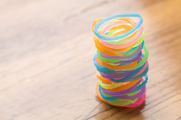 Colored rubber bands on wooden table