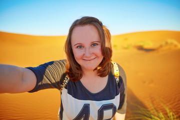 Happy tourist taking selfie in Sahara