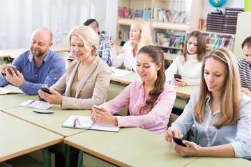 Adult students with smartphones in classroom.