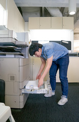 woman inserting paper in laser printer cartridge in office