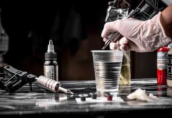 Hands of  tattooist create a tattoo