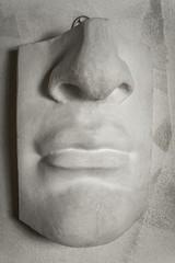 Part of male face sculptured in stone.