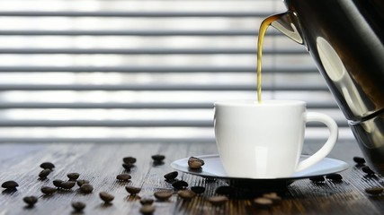 pour coffee into the cup on the kitchen table