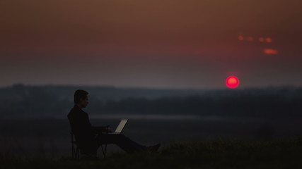 Man sits by sunset (sunrise) background on the top of the hill