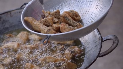 frying pieces of fish in hot oil
