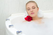 beautiful woman relaxing in bath with flower and candles