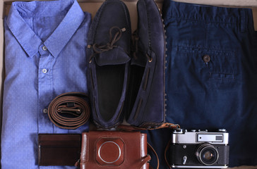 Set of male casual clothing, and retro photocamera in a box