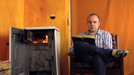 Man read study book near warming stove fire place. Glass of wine