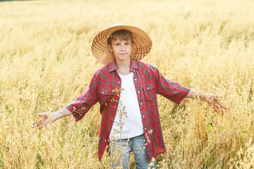 Portrait of walking teenage boy in wide-brimmed straw hat